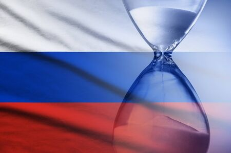 Hourglass with running sand superimposed over a Russian flag conceptual of a countdown, deadline or time management