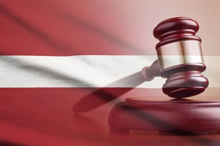 Legal gavel on its plinth over a flag of the Latvia in a conceptual composite image