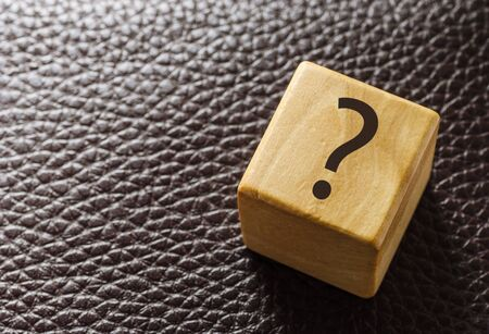 Wooden toy block with question mark on leather