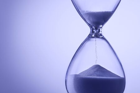 Blue toned hourglass with running sand measuring the passage of time in a deadline or countdown concept with copy space