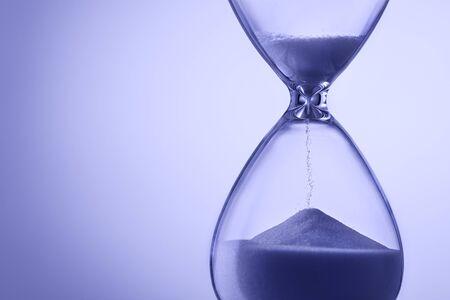 Sablier aux tons bleus avec du sable courant mesurant le passage du temps dans un concept de date limite ou de compte à rebours avec espace de copie