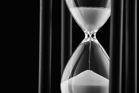 Sand running through a clear glass hourglass between the bulbs measuring the passage of time in a countdown concept with copy space on black