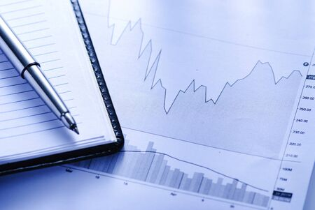 Open journal with business graphs and pen in a business accounting or statistical analysis concept in close up