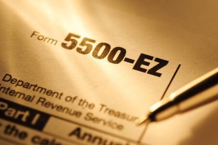 United State IRS form 5500-EZ in close up in sunlight with a pen for completion and submission to the Treasury Department