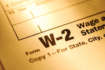 Close up on a Form W-2 Wage and Tax statement form for the US Treasury or IRS with focus to the title in yellow light