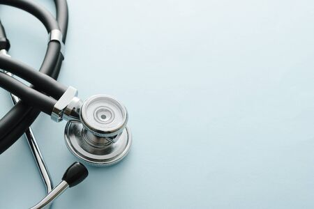 A coiled stethoscope with focus to the acoustic disc on white with copy space in a medical, healthcare or Covid-19 pandemic concept viewed from above Stock Photo