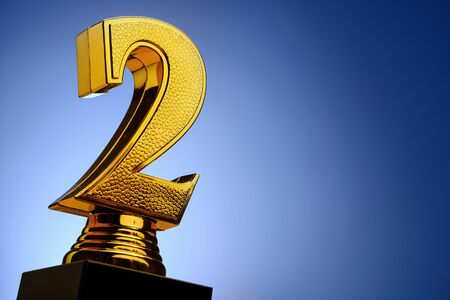 3d textured gold number 2 trophy award on blue in close up to the side with copy space for the second place runner-up in a competition or race