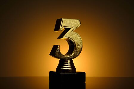 Gold number three trophy for the third placed runner up in a competition or sporting race over a brown background with orange highlight and copy space