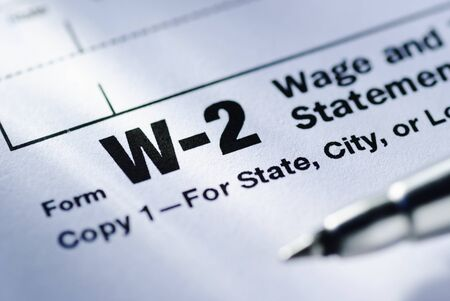 Pen on a Form W-2 Wage and Tax Statement for the US Treasury to be submitted by the employer in close up in a conceptual financial image
