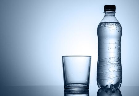 Plastic bottle of sparkling water with empty clean tumbler or glass alongside in a low angle side view with copyspace Stock Photo