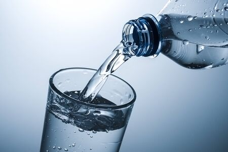 Sparkling water being poured into a tall glass in a close up on the neck of the plastic bottle and rim of the tumbler