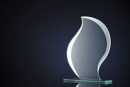 Stylish flame shaped glass trophy with copyspace for engraving the name of the winner on the plaque over a dark Stock Photo
