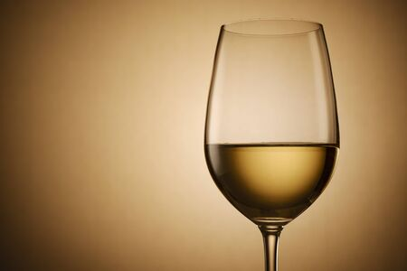 Glass of white wine over a graduated brown background with central highlight in a side view close up with copy space