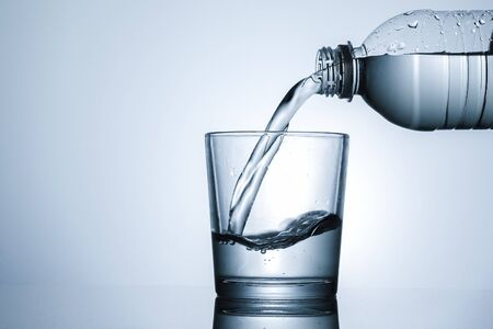 Pouring water into a tumbler in close up on the neck of the bottle and liquid with splash over grey with copyspace
