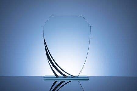Elegant blank glass shield trophy on dark blue background ready to be engraved for the winner of a competition or race