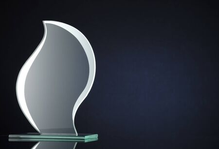 Stylish flame shaped glass trophy with copyspace for engraving the name of the winner on the plaque over a dark background Stock Photo