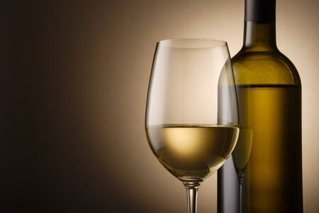 Unlabelled bottle and glass of white wine side by side highlighted over a shadowy brown background with copy space in a cropped close up Stock Photo