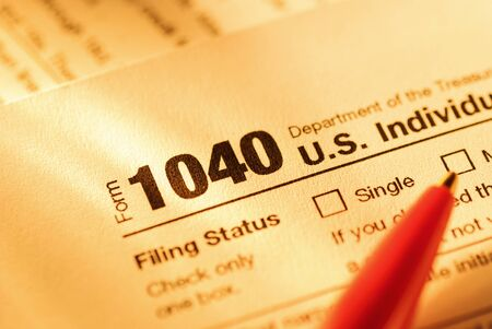 Form 1040 with red pen for US tax declaration of Individual Income in close up in yellow light in a financial and taxation concept