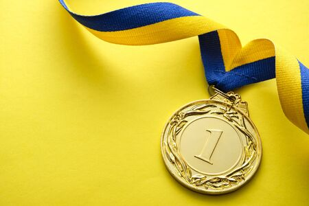 Gold medallion for the winner or champion in a competition or race on a blue and yellow twirled ribbon over a matching yellow background with copyspace Stock Photo