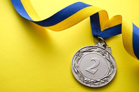 Silver medallion for the 2nd place runner up in a competition or race on a blue and yellow twirled ribbon over a yellow background with copyspace