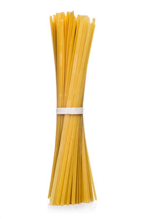 Bundle of dried Italian spaghetti pasta tied in the center standing upright on white with lateral copyspace Stock Photo