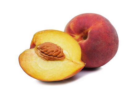 Whole and halved juicy ripe fresh peach showing the pip on a white background in a healthy diet concept Stock Photo
