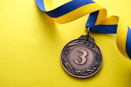 3rd place bronze medallion for a runner up in a competition or race on a blue and yellow twirled ribbon over a matching yellow background with copyspace Stock Photo