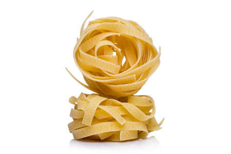 Two coils of dried Italian ribbon pasta or noodles on white with copy space with one upended on the other Stock Photo
