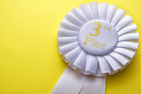 3rd place runner up white rosette with central gold text place to be awarded in a competition or race on a yellow background with copyspace