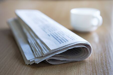Folded newspaper on a wooden table with a cup of tea or coffee in the background and focus to the front of the paper