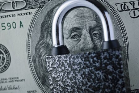 Padlock lying on a dollar bill on portrait of Franklin with focus to his eyes through the steel shank in a financial security concept Stock Photo