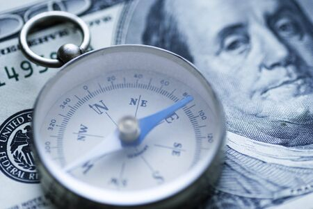 Small metal compass pointing to East lying on dollar bills in close up in an economic or financial concept