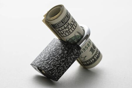 Roll of dollar bills threaded through a padlock shank resting at an angle on a white background in a financial security concept Stock Photo
