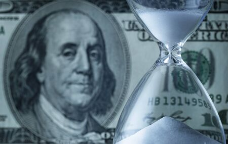 Dollar bill with egg timer or hourglass with running sand in a financial countdown or deadline concept in a closeup cropped view