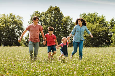 Young family with kids running hand in hand through a field or wildflowers in spring or summer approaching the camera in a healthy outdoor lifestyle concept Foto de archivo