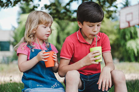 Two young children enjoying a healthy fruit drink in colorful mugs outdoors in the shade of a tree with a young brother and sister sitting side by side
