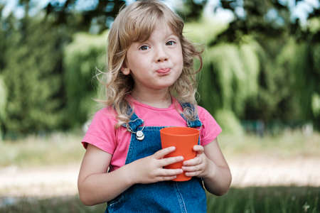 Cute little blond girl pursing her lips as she drinks juice from a colorful red mug outdoors in the garden in summer in close up
