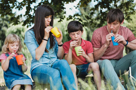 Young family with children relaxing outdoors drinking juice from colorful mugs in the shade of a leafy green tree