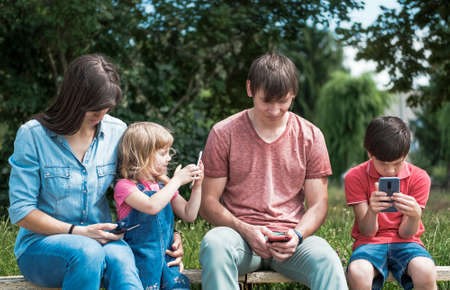 Young parents relaxing outdoors with their kids, a little girl and boy, seated on a bench in a park looking at their mobile phones