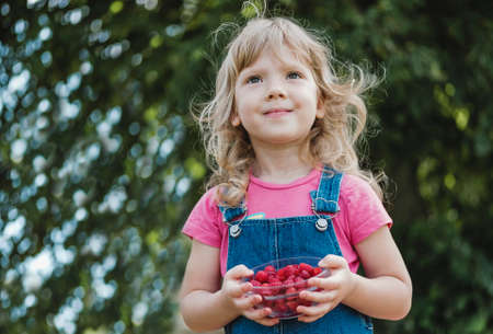 Smiling young blond girl holding a bowl of fresh ripe juicy raspberries in a low angle view outdoors against green leaves