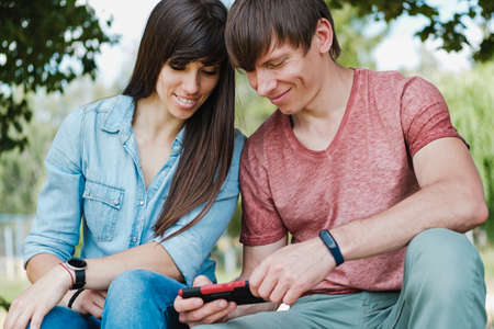 Young couple smiling as they read a phone message or watch media on their mobile sitting side by side outdoors in the garden