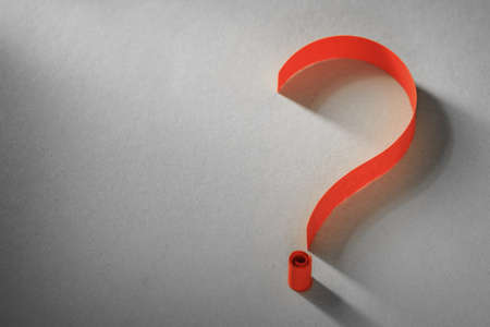 Colorful bright orange coiled paper question mark on a grey background with copyspace conceptual of a search, research, help or query