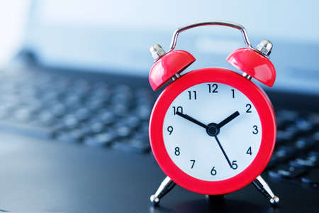 Red alarm clock on a computer keyboard, with a blurred background and a shallow depth of field. Stock Photo