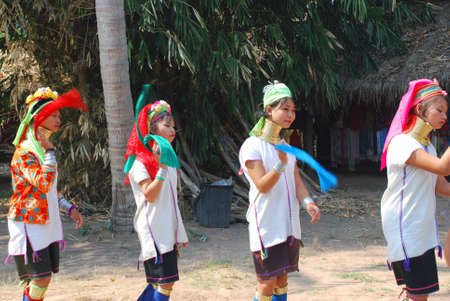 This photho was taken in Thailand on January, 2011. Girls from a tribe Karen carry out original dance for endless tourists. To each his own, life is going on. Girls which do not have an alternative in life. Редакционное