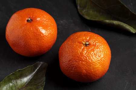 Mandarin, black background. Fresh tangerine fruit with green leaf, dark mood. Clementine citrus plant, healthy, natural, organic. Christmas harvest, healthy vegetarian tangerines closeup
