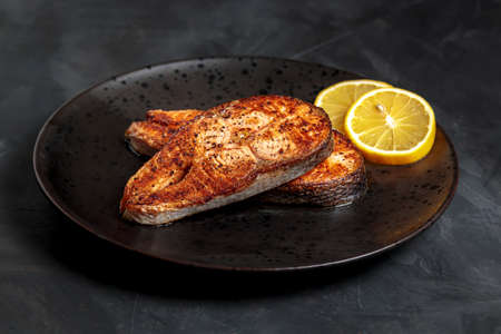 Fried salmon steak, healthy lunch dish. Roasted trout steak closeup, omega 3 nutrition appetizing with lemon on plate. Fatty norwegian salmon slice, restaurant entree concept, above side Banque d'images