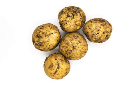 Organic potato isolated on white background, top view. Natural potato pile with earth ground, country agriculture plant stack. Dirty whole potatoes harvest, vegan garden ingredient
