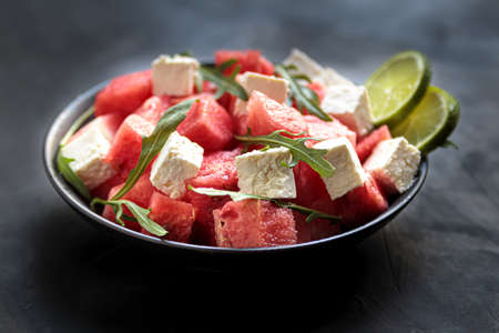 Watermelon salad with feta cheese, arugula, lime in bowl. natural helthy cuisine, fresh and tasty vegetable lunch. Mediterranian eating, cool dinner in plate without meat