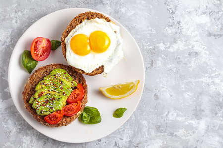Avocado toast breakfast with fried egg, top view. Fresh avocado burger, vegetarian snack, delicious dark bread, natural avocado slices on plate. Gourmet diet appetizer 版權商用圖片