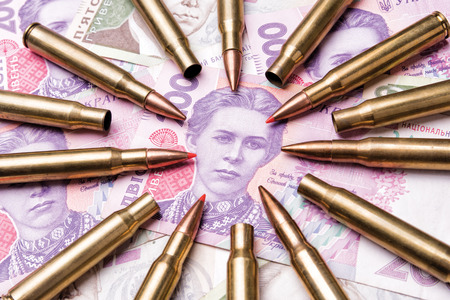 The ammunition cartridges are aimed at the banknotes of Ukrainian hryvnia. The symbol and concept of danger and war in the country Stok Fotoğraf